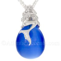 Sterling Silver Mermaid Pendant Sitting on Dark Blue Cateye Stone